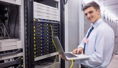Smiling technician using laptop while analysing server