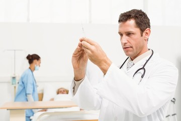 Doctor holding injection with colleagues and patient behind
