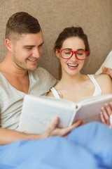 Cute couple reading book in bed