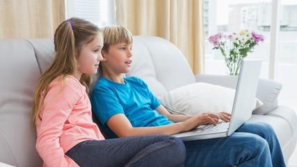 Happy siblings using laptop on sofa