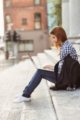 Young student using her laptop to study outside
