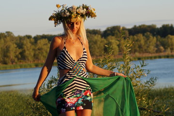 Девушка с венком на голове стоит на бревне около болото