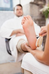Pedicurist massaging customers foot