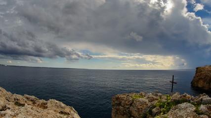 memorial cross on sea cliff  sunbeams on island of Majorca