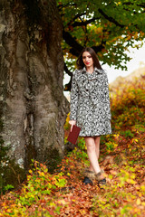 beautiful woman with a book in hand walking in the park