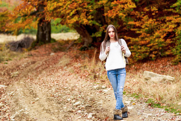 young woman with backpack hiking during autumn