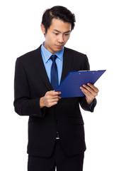 Businessman read on clipboard