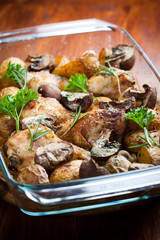 Baked chicken on potatoes and mushrooms