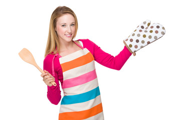 Housewife with wooden spatula and heat insulation gloves