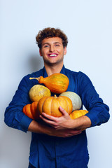 Happy man holding pumpkins over blue background