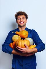 Happy man holding pumpkins over blue background