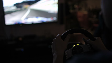 Playing racing game with steering wheel simulator