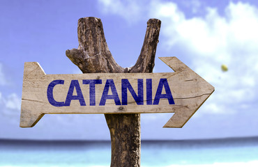 Catania wooden sign with a beach on background