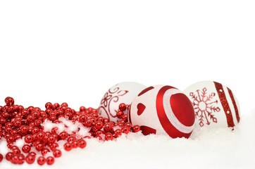 christmas background with balls and red garland in snow on white