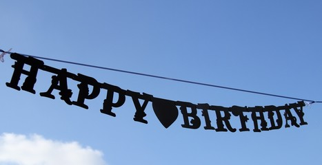 HAPPY BIRTHDAY sign hung on the blue sky