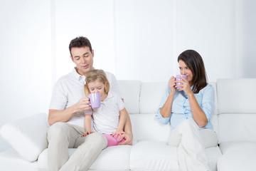 family having breakfast on sofa