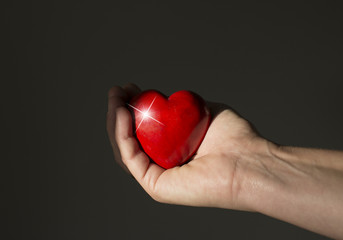 red heart shining in womans hand