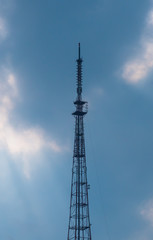 Telecommunications tower on the background of cloudy sky.
