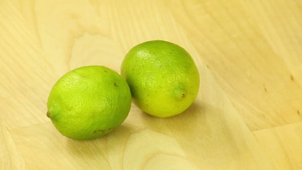 Two lime rotate on the background of wooden boards