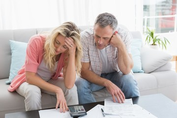 Worried couple calculating bills on the couch