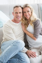 Happy casual couple sitting on rug smiling at camera