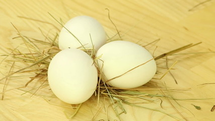 Three eggs are rotated on a background of wooden boards