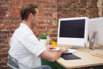 Creative worker typing on laptop at his desk