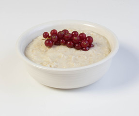 Bowl of oats porridge with red currant  on a white background