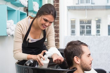 Hair stylist putting conditioner in mans hair