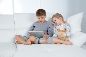 brother and sister on white sofa