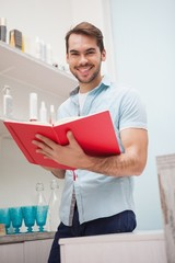 Smiling hairdresser with stock book