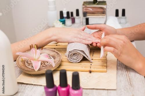 Leinwanddruck Bild Nail technician giving customer a manicure