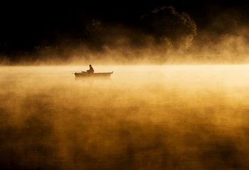 Early morning sunrise, boating on the lake in a huge fog