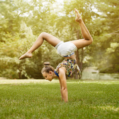Young girl doing stretching exercise on green grass at park