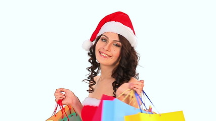 Woman in Santa hat holding shopping bag.