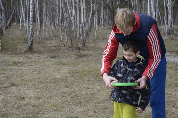 Spring in the forest on a glade father teaches his son to throw