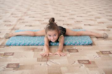 Little girl doing leg-split on the floor