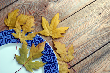 Plate and maple leaves on a wooden table