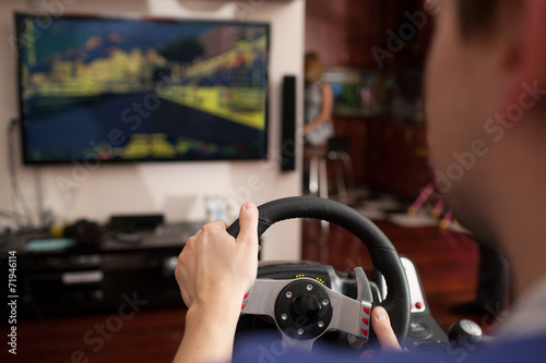 Man playing racing game with steering wheel simulator - 71946114