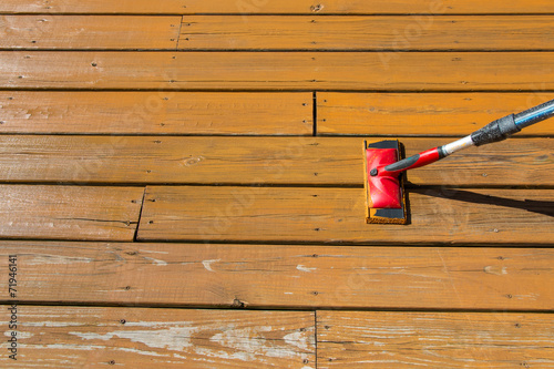 Wood stain with a paint pad  on wooden patio floor - 71946141