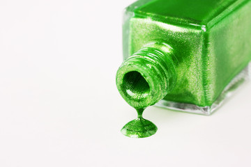 Green nail varnish dripping on white background