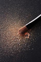 Powder scattered on black background from make up brush