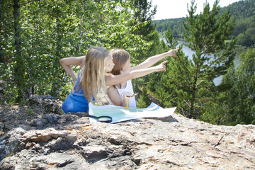 Two Young Girls   in Mountain read the Map near  River