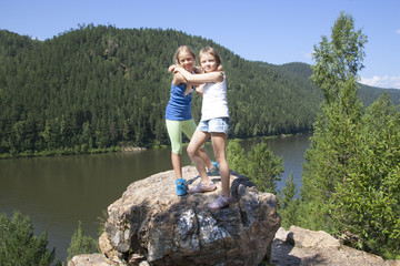 Two girls standing on a rock and enjoying river  view