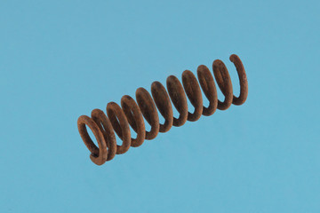 Close up photo of  a steel spring on a blue background.