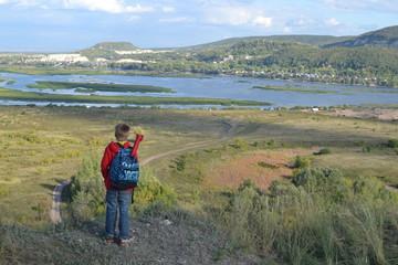 Маленький турист стоит на холме
