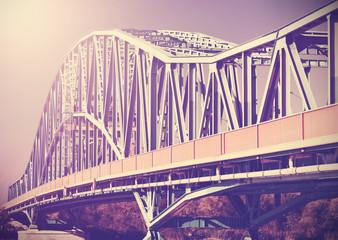 Vintage stylized photo of a steel bridge with sun light.