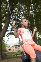 Young girl with dark skin on tyre swing