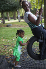 Young girl with dark skin pushing her mother on tyre swing