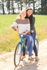 Two happy girls ride bicycles on countryside
